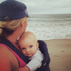 A woman with a baby strapped to her chest, the woman is looking away from the camera at the ocean behind her, and the baby is looking sweetly at the camera.