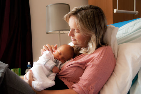 Mumma with a newborn baby sleeping on her chest, she is sitting up on a hospital bed, stoking the base of the baby's back and looking down with love.