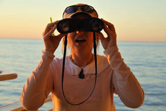 Woman forward-facing the camera, holding binoculars in front of her eyes, on the bridge of a ship with the sun setting over the ocean behind her.