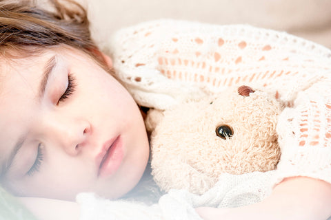 A small girl with brown hair is asleep in this image, clutching a soft brown teddy bear, both look peaceful
