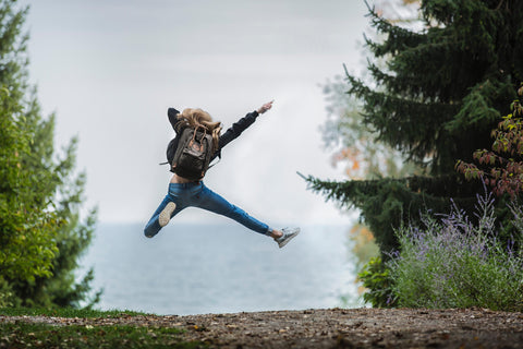 A nature pathway leads into the distance which is lined with fir trees, in the middle of the pathway and middle distance of the image there is a person seen from behind and they are leaping into the air with their arms and legs outstretched in joy.