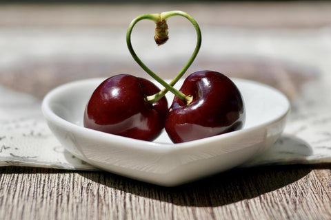Two lusciously plump red cherries are nestled in a heart shaped white dish on a natural timber background and the stems of the cherries remain connected and are woven into a heart