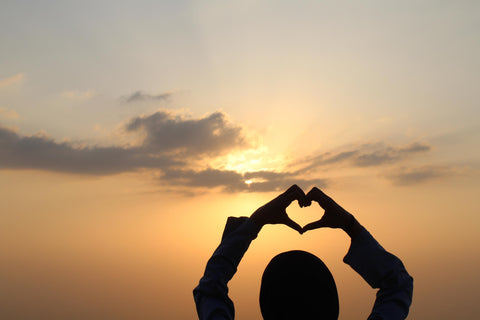 The silhouette of the back of a person's head with their arms held above their head and their hands are creating a love heart shape, and there is a golden sunset as the backdrop of the image, with a few lazy clouds in the sky