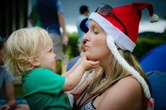 2 year old boy sitting on his mumma's lap, they are facing each other but are side on to the camera, his mumma is wearing a santa hat and the child is squeezing her face as they play with each other.