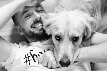 Smiling man wearing a hope shirt with a dog laying on him