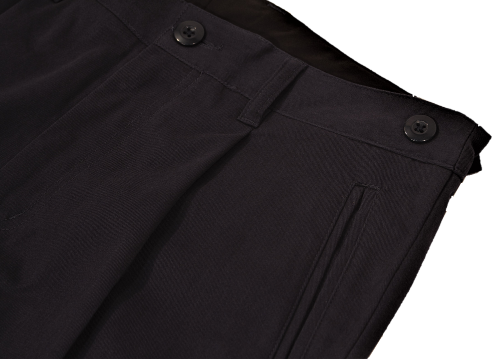 Close-up view of navy pants to demonstrate detailing of single pleat and expandable side button adjustment