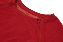 Load image into Gallery viewer, Close-up view of raglan-sleeve top in tomato color demonstrating detailing of ribbed crew-neck trim, zipper pull covers, and fabric texture
