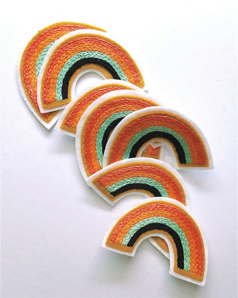 Colorful hand embroidered rainbow patch pile