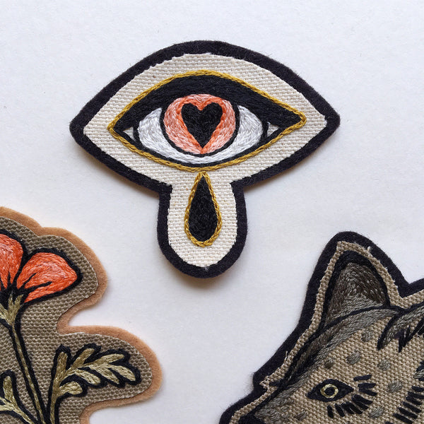 A collection of hand embroidered patches in peach black and tan