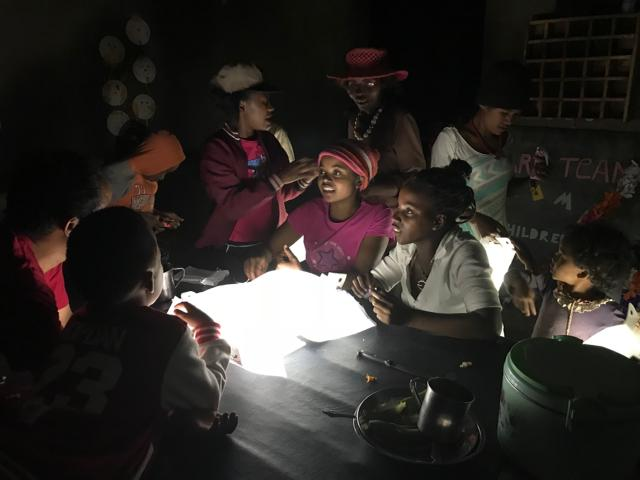Girls using a LuminAID solar lantern at night