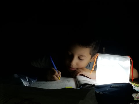 Young boy studies in Puerto Rico with LuminAID solar lantern