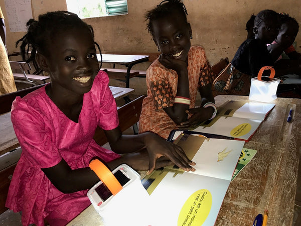 Girls in Senegal reading by LuminAID solar light