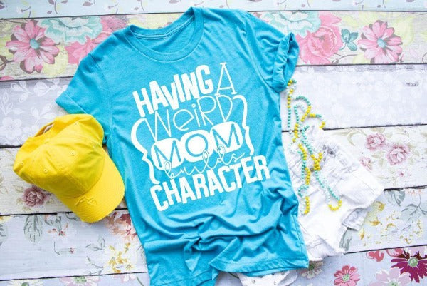 "(1) Short sleeve shirt ""Having A Weird Mom Builds Character"" (accessories in the photo are not included)."