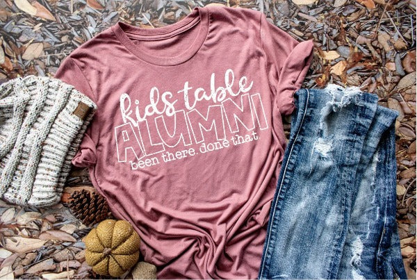 "(1) Short sleeve shirt ""Kids Table Alumni Been There Done That"" (accessories in the photo are not included)"