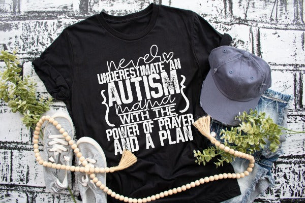 "(1) Short sleeve shirt ""Never Underestimate An Autism Mama With The Power Of Prayer And A Plan"" (accessories in the photo are not included)."