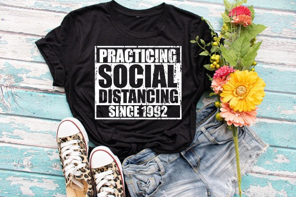 "(1) Short sleeve shirt ""Practicing Social Distancing Since 1992"" (accessories in the photo are not included)"