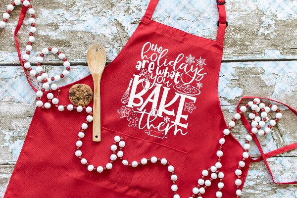 "(1) Red Apron with ""The Holidays Are What You Bake Them Apron"" image. (Accessories in the photo are not included)."