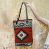 Woman Showing Adobe Red Wool Tote Bag With Mint Green God's Eye Design And Black Leather Straps