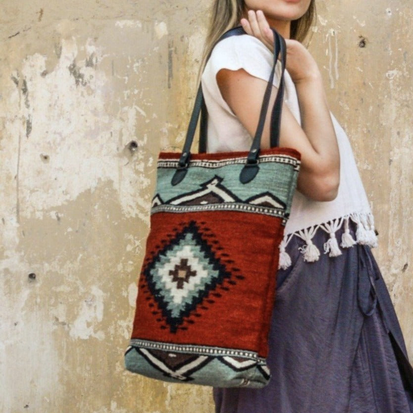 Woman Holding Adobe Red Wool Tote Bag With Mint Green God's Eye Design And Black Leather Straps
