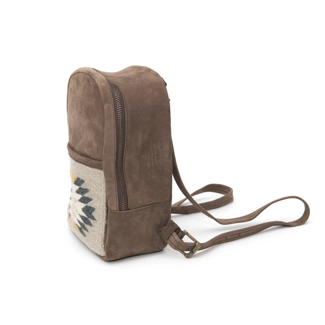 Sideview of Brown Leather Mini Backpack with Woven Pocket Featuring Zapotec Design In Blue And Gray
