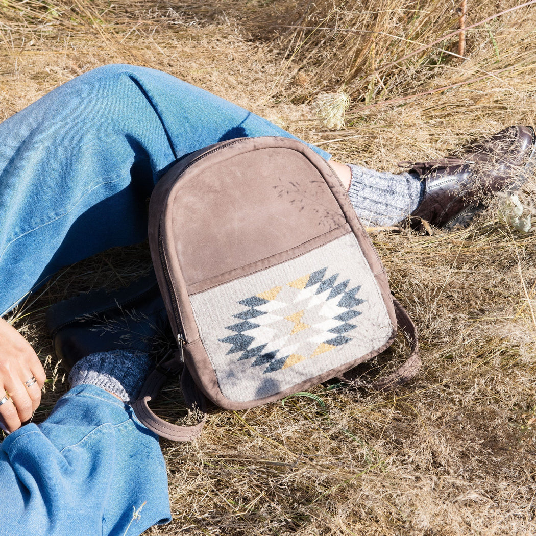 Brown Leather Mini Backpack with Woven Pocket Featuring Zapotec Design In Blue And Gray In Grassy Field