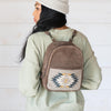 Woman Wearing Brown Leather Mini Backpack with Woven Pocket Featuring Zapotec Design In Blue And Gray