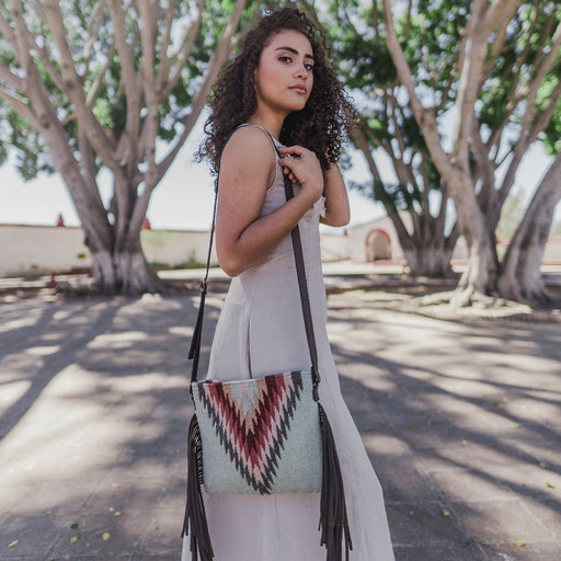 Woman Modeling Mint Green Wool Crossbody Purse with Zapotec Lightning Design In Pink Shades, With Brown Leather Fringe And Brown Leather Strap