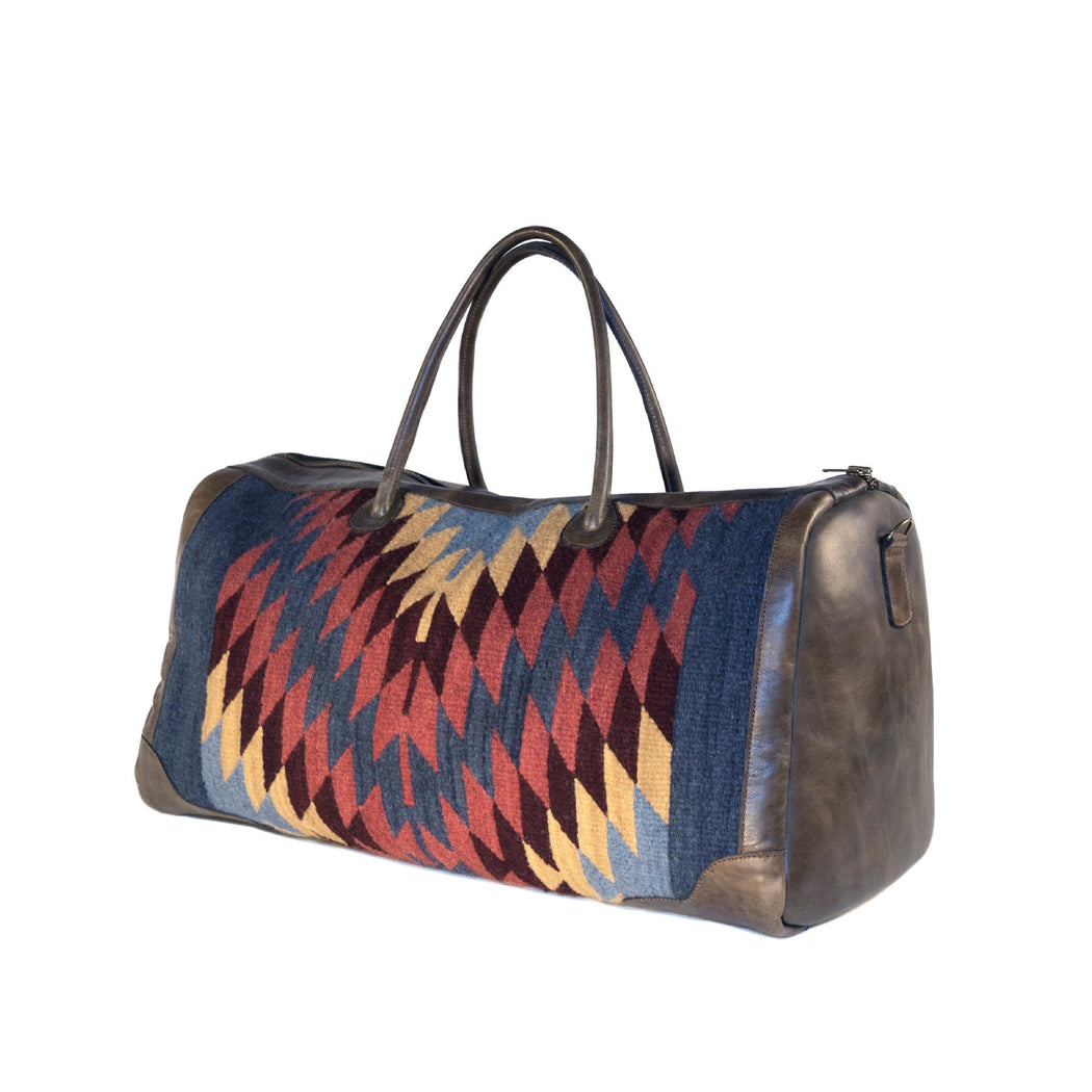 Three Quarter View Of Brown Leather Duffel Bag With Woven Panels Of Zapotec Diamond Designs In Red, Blue, And Yellow