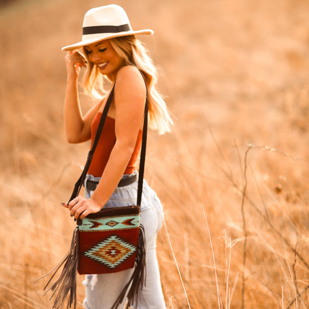 Woman Wearing Brick Red Wool Crossbody Purse With Turquoise Zapotec Diamond And Arrow Designs And Brown Leather Fringe