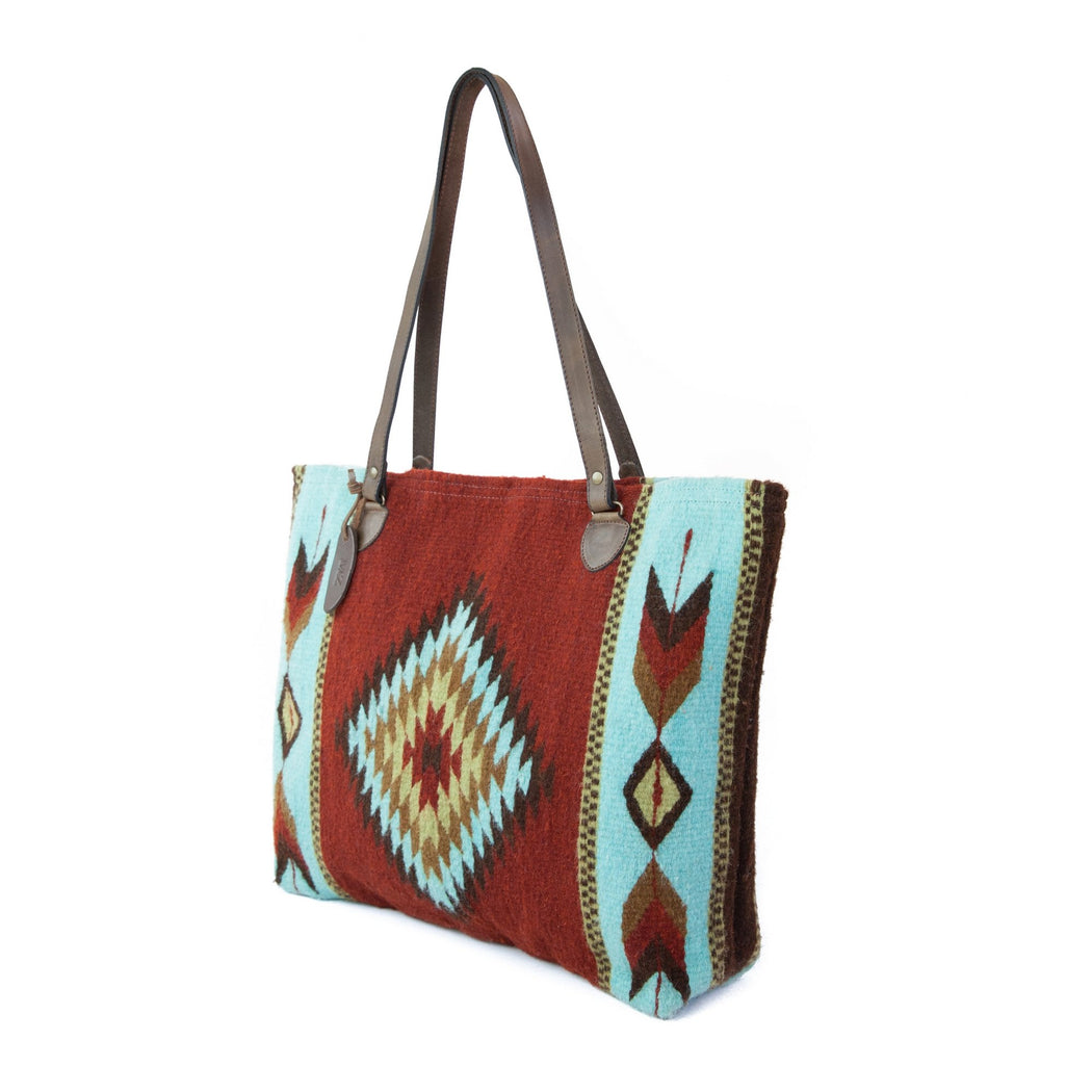 Three Quarter View Of Brick Red Wool Tote Bag With Zapotec Diamond & Arrow Designs And Brown Leather Strap