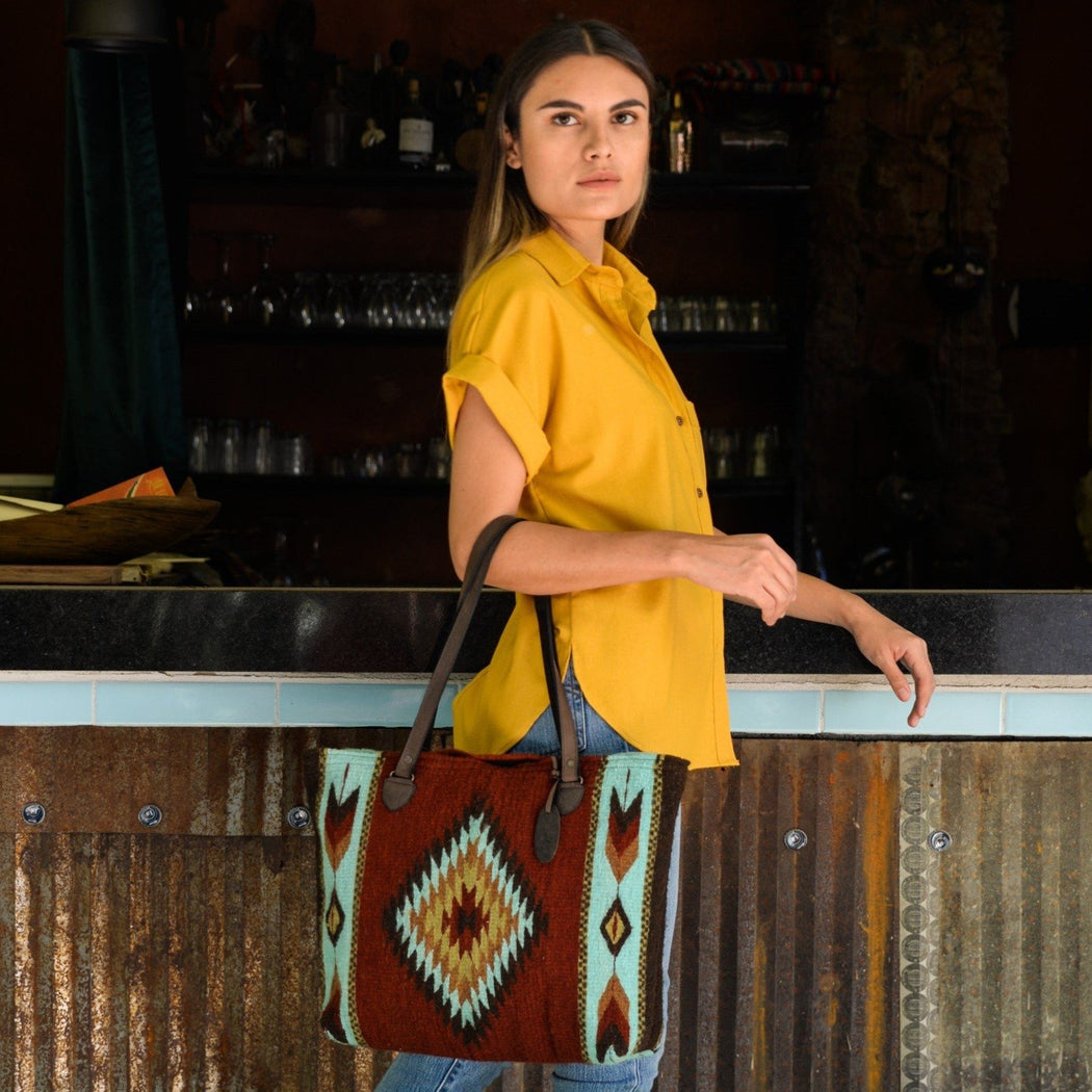 Woman Carrying Brick Red Wool Tote Bag With Zapotec Diamond & Arrow Designs And Brown Leather Strap