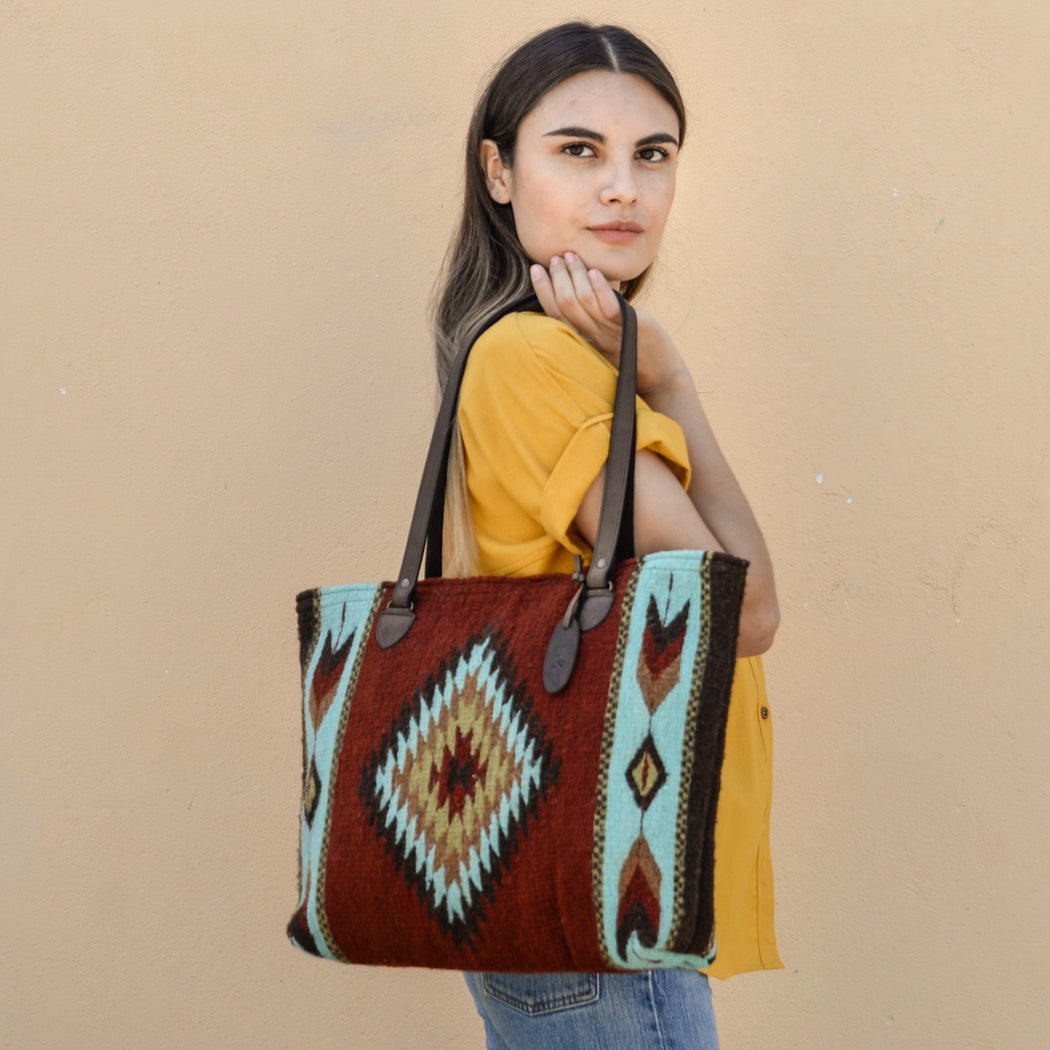 Woman Holding Brick Red Wool Tote Bag With Zapotec Diamond & Arrow Designs And Brown Leather Strap