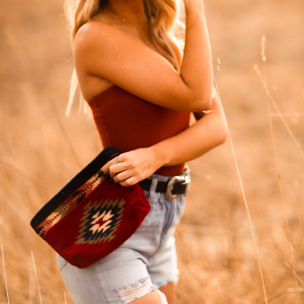 Woman Holding Brick Red Wool Clutch With Zapotec God's Eye Design
