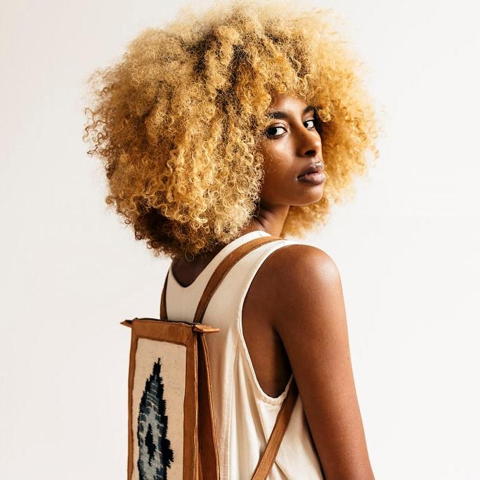 Model Wearing Blonde Leather Backpack With Zapotec Diamond Designs In Indigo And Blue On Cream Wool Panel