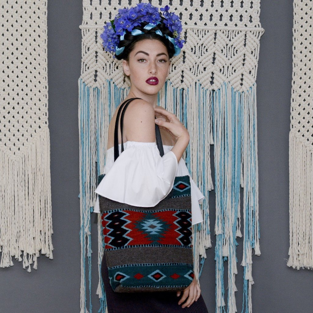 Model Carrying Gray Wool Tote Bag With Zapotec Diamond Designs In Turquoise Navy And Red With Black Leather Straps