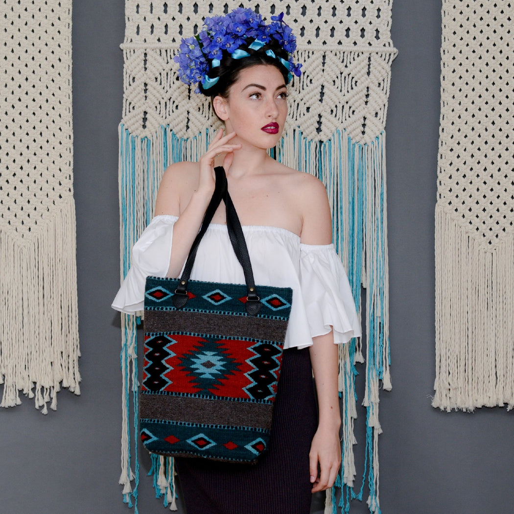 Woman Holding Gray Wool Tote Bag With Zapotec Diamond Designs In Turquoise Navy And Red With Black Leather Straps