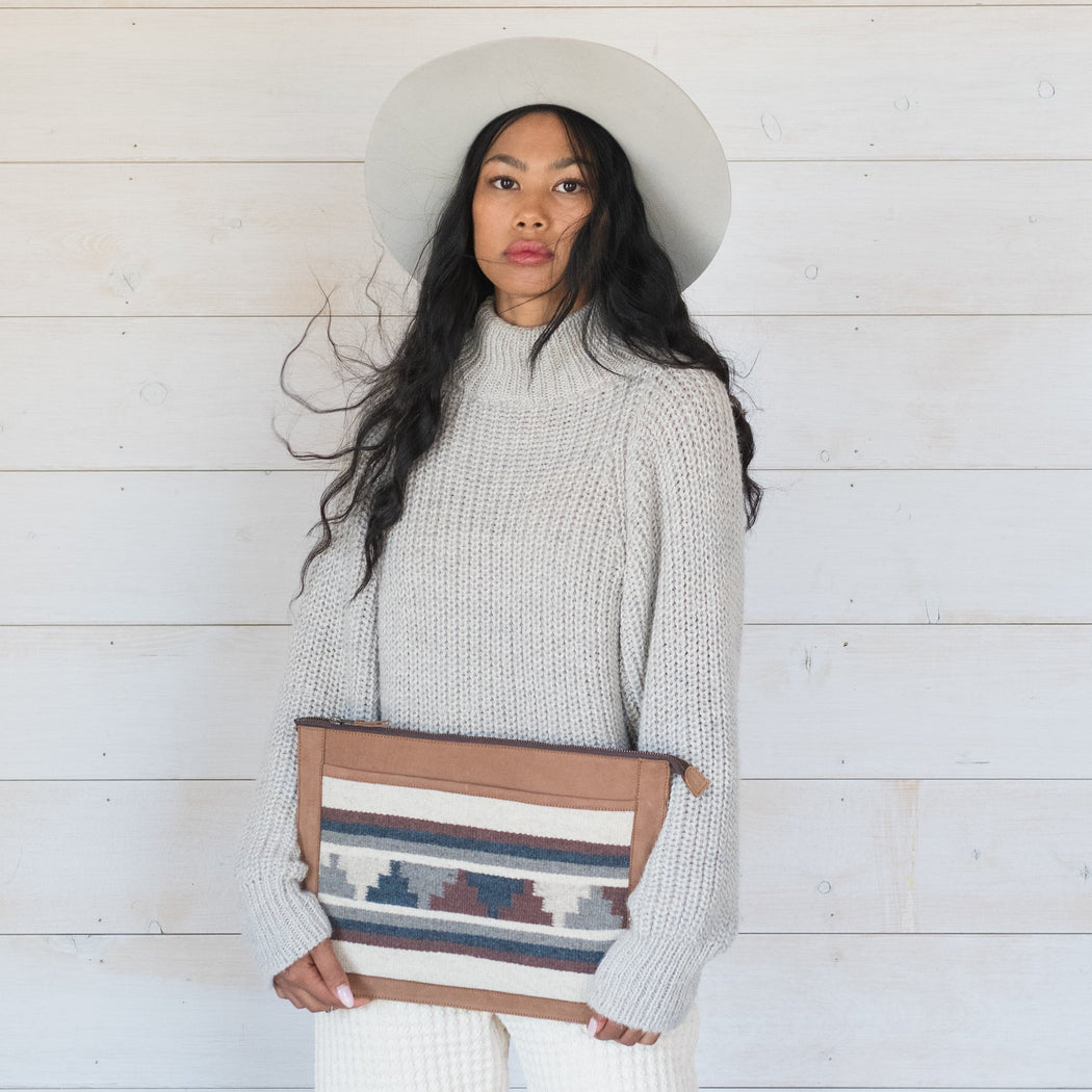 Model Holding Blonde Leather Laptop Sleeve With Zapotec Mitla Designs In Blue, Gray, Cognac And Cream On Wool Panel
