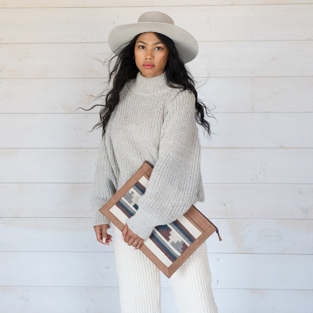 Woman Carrying Blonde Leather Laptop Sleeve With Zapotec Mitla Designs In Blue, Gray, Cognac And Cream On Wool Panel