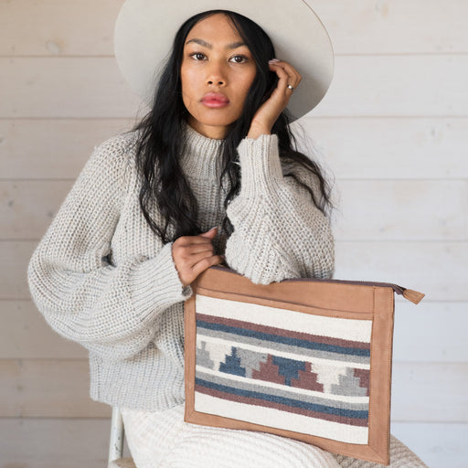 Model With Blonde Leather Laptop Sleeve With Zapotec Mitla Designs In Blue, Gray, Cognac And Cream On Wool Panel