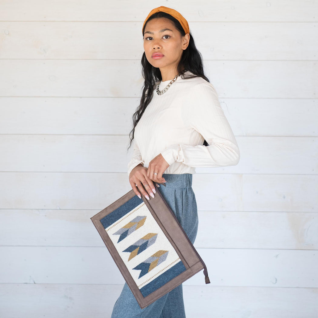 Model Holding Brown Leather Laptop Sleeve With Zapotec Arrow Designs In Blue, Gray, Yellow And Cream On Wool Panel