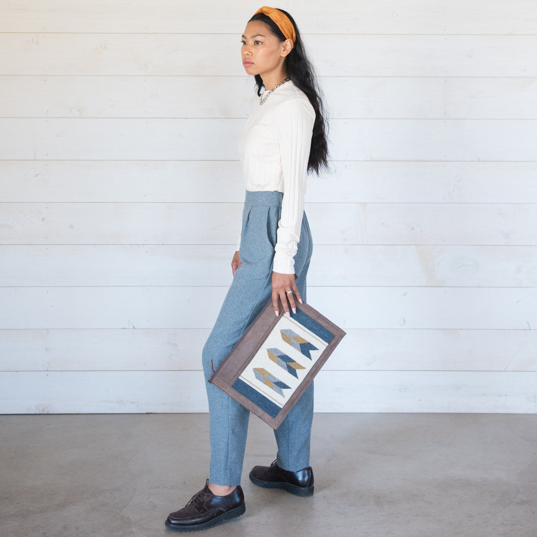 Woman Holding Brown Leather Laptop Sleeve With Zapotec Arrow Designs In Blue, Gray, Yellow And Cream On Wool Panel