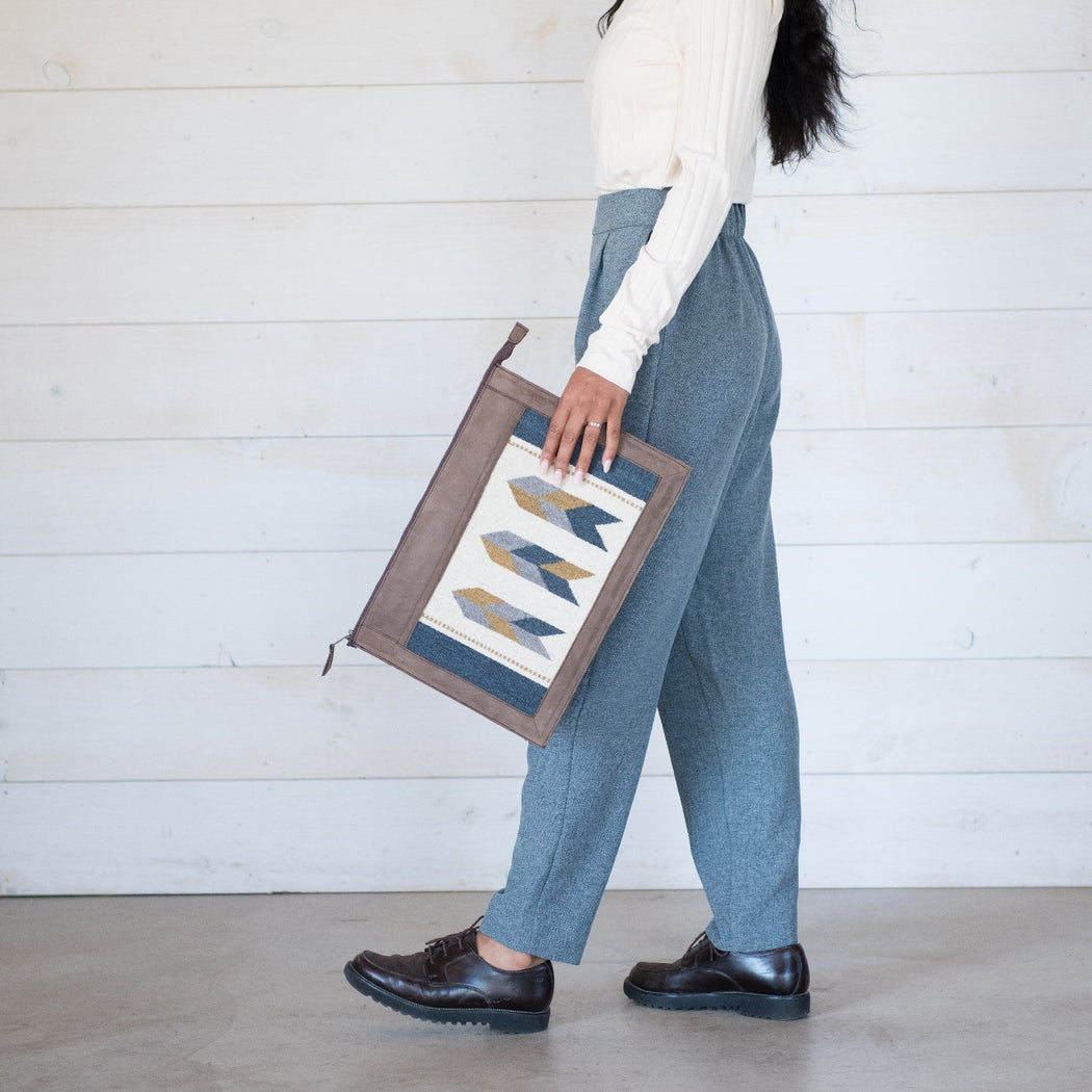 Woman Carrying Brown Leather Laptop Sleeve With Zapotec Arrow Designs In Blue, Gray, Yellow And Cream On Wool Panel