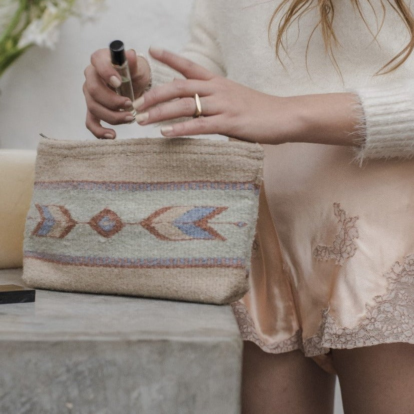 Model Using Beige Wool Clutch Purse With Zapotec Arrow Designs In Powder Blue, Cool Mint & Dusty Rose