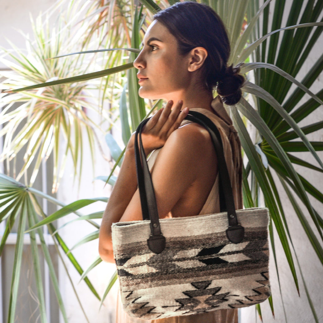 Woman Modeling Wool Shoulder Bag With Zapotec Agave, Arrow & Lightning Designs In Tan, Brown, Cream And Gray With Brown Leather Straps