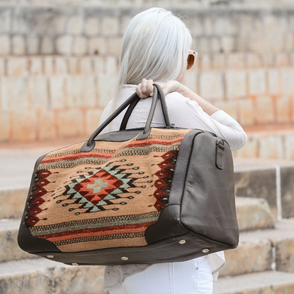 Model Carrying Brown Leather Duffel Bag With Zapotec Diamond & Agave Design In Robin's Egg Blue, Coral And Brick Red, On Beige Wool