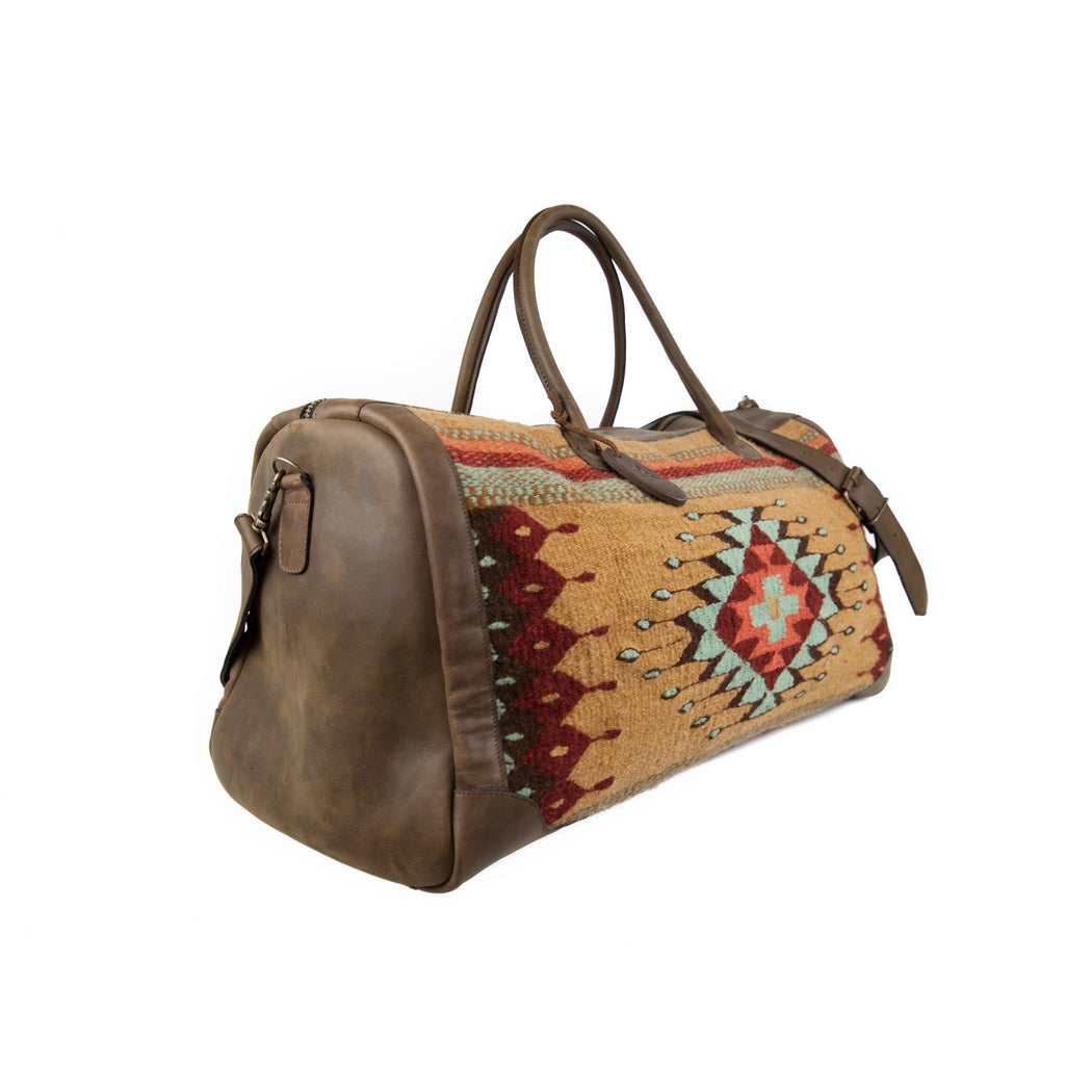 Three Quarter View Of Brown Leather Duffel Bag With Zapotec Diamond & Agave Design In Robin's Egg Blue, Coral And Brick Red, On Beige Wool
