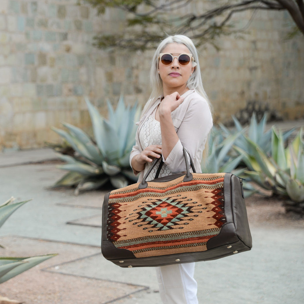 Woman Carrying Brown Leather Duffel Bag With Zapotec Diamond & Agave Design In Robin's Egg Blue, Coral And Brick Red, On Beige Wool