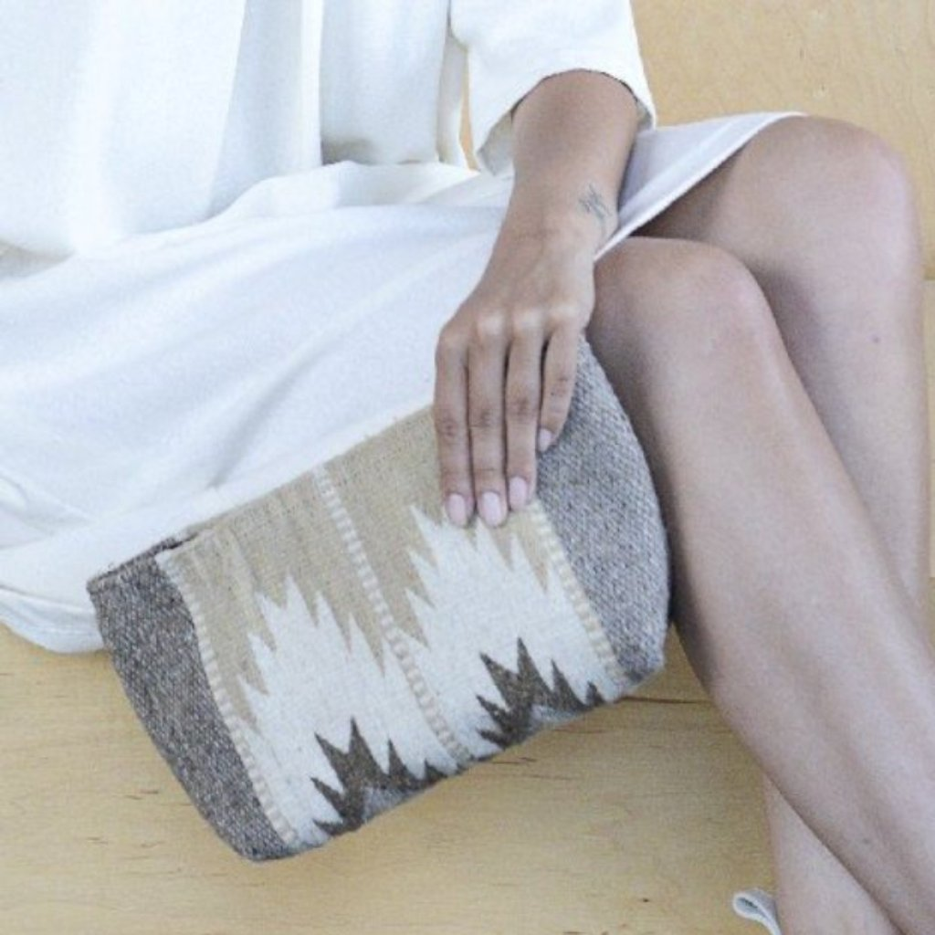 Close Up Of Woman Holding Wool Clutch Purse Featuring Zapotec Lightning Design In Shades Of Brown, Tan And Cream