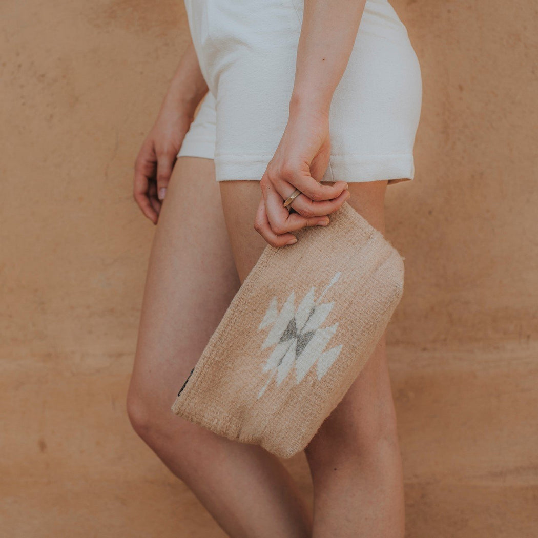 Close Up Of Woman Carrying Wool Clutch Purse Featuring Zapotec Diamond Design In Soft Cream On Pink