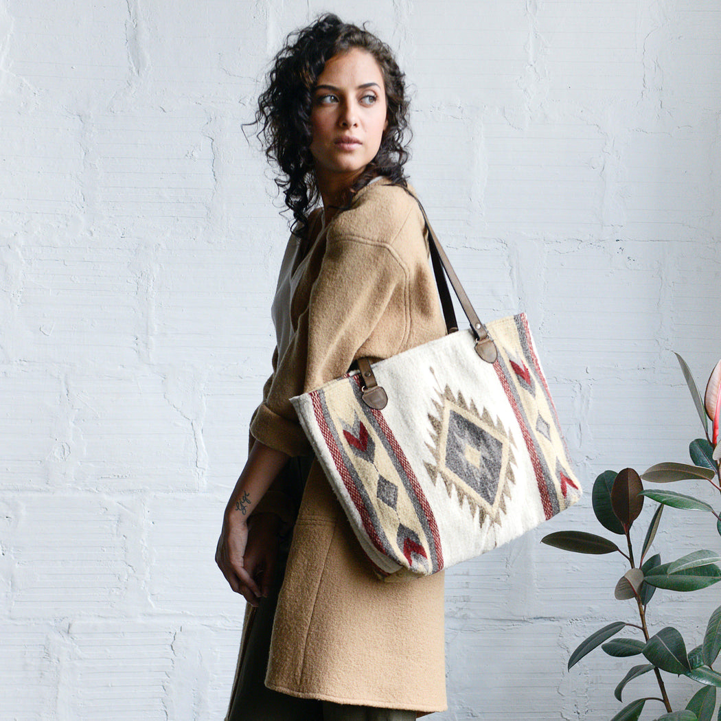 Woman Holding Wool Tote Bag Featuring Zapotec Diamond And Arrow Design In Cranberry, Sage Green And Beige On Cream With Brown Leather Straps